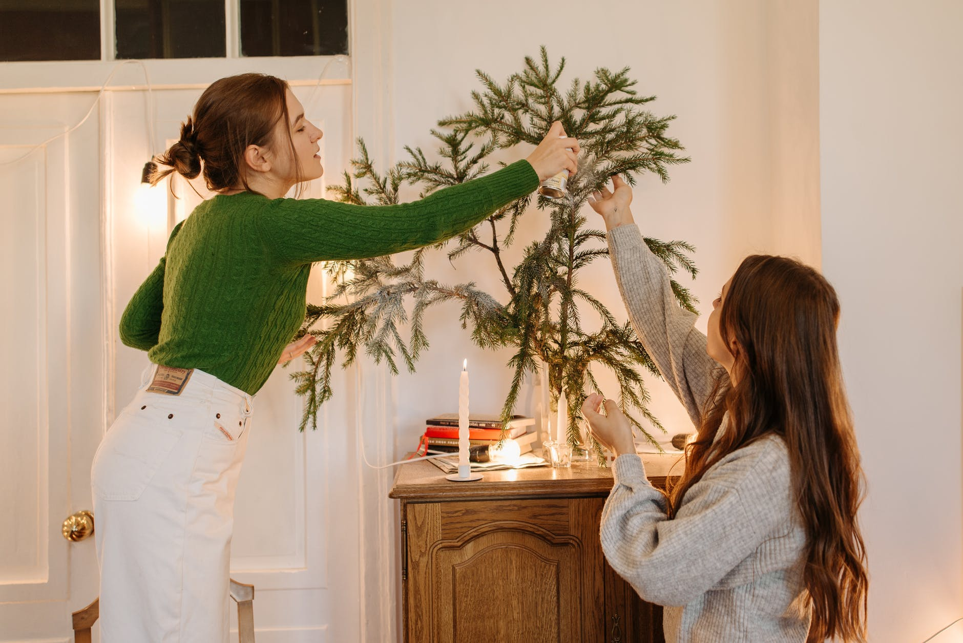 two girls decorating a christmas tree