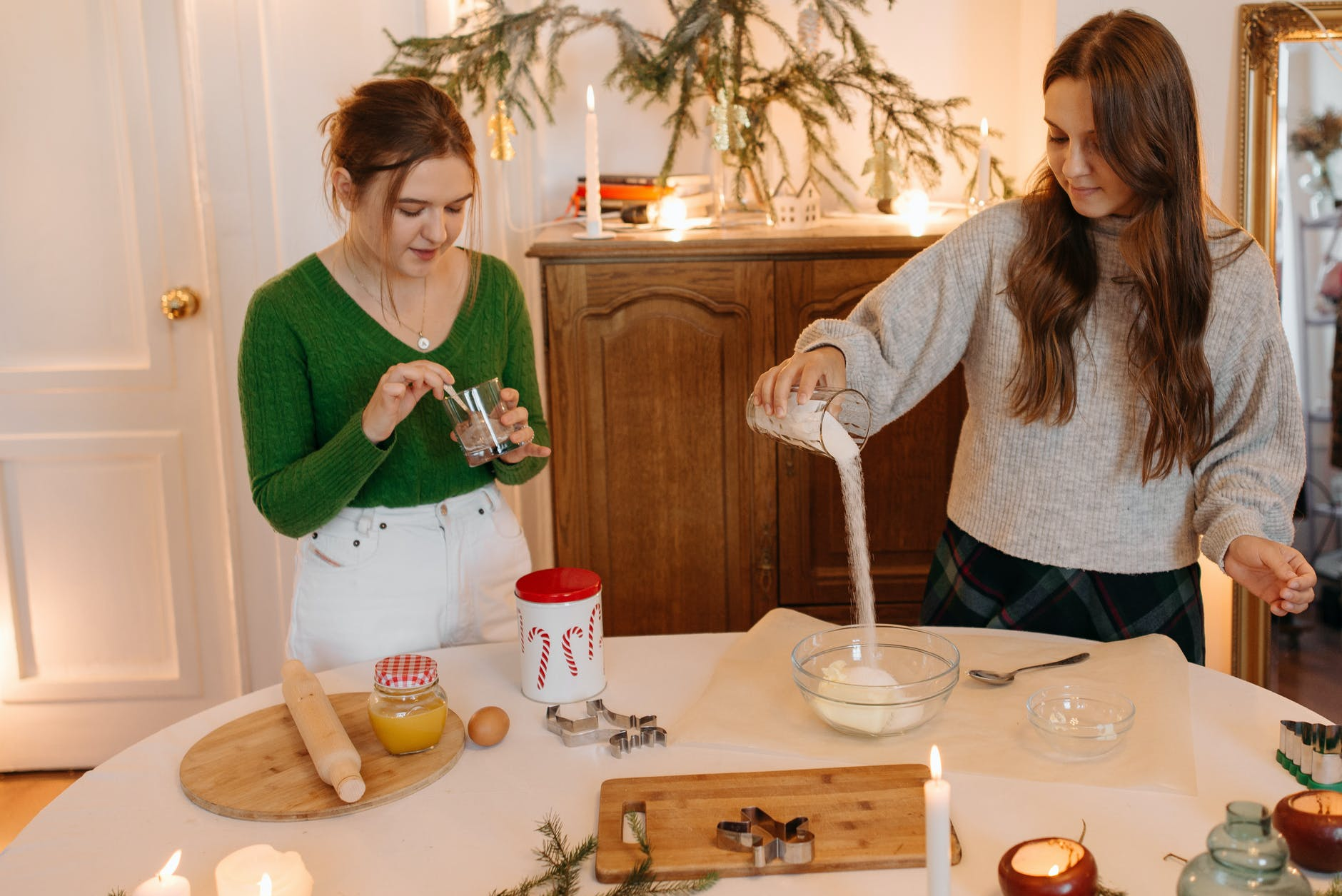 two girls preparing ingredients to bake christmas cookies