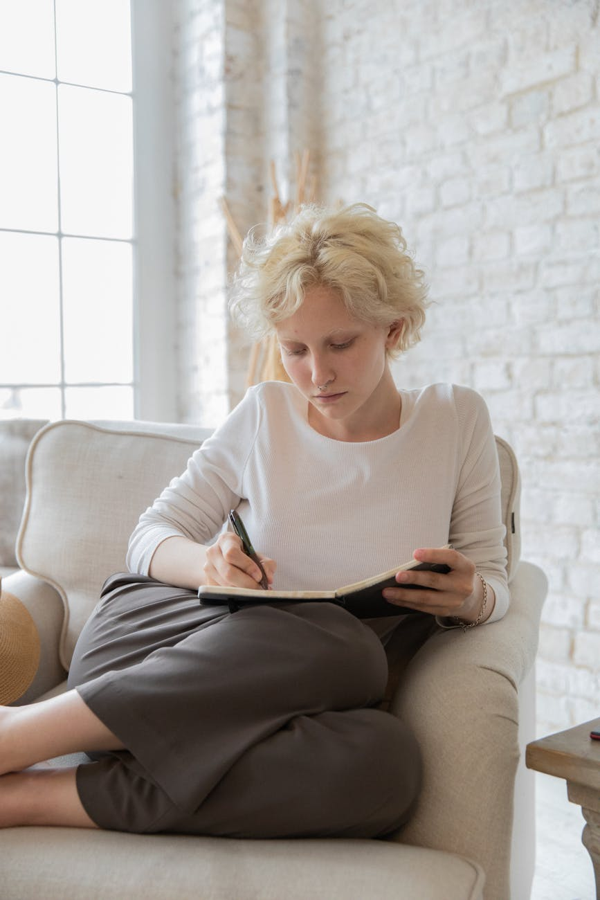focused young lady writing thoughts in notebook while relaxing in armchair